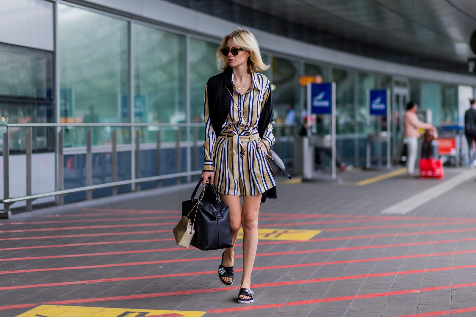 DUESSELDORF, GERMANY - JUNE 1: Lisa Hahnbueck at the airport wearing a striped blouse and shorts from Finders Keepers, black Celine sunglasses, a black scarf a black weekender bag from Aigner Munich and golden bag and Marc Cain slippers on June 1, 2016 in Duesseldorf, Germany. (Photo by Christian Vierig/Getty Images) *** Local Caption *** Lisa Hahnbueck