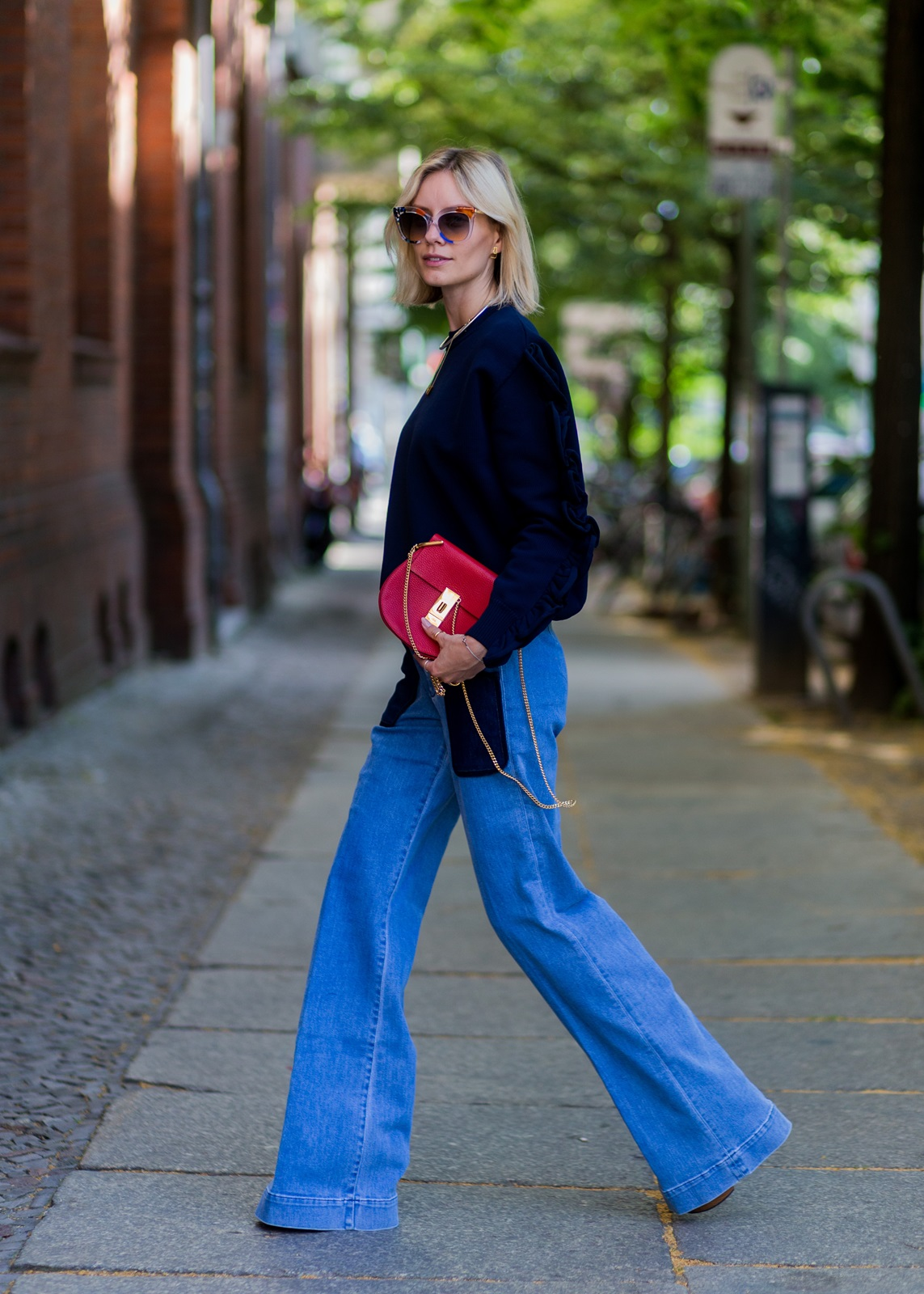 BERLIN, GERMANY - JUNE 28: Lisa Hahnbueck wearing Fendi sunglasses, wide leg denim pants, a navy jumper from Victoria Beckham, red Chloe bag and Guess heels during the Mercedes-Benz Fashion Week Berlin Spring/Summer 2017 on June 28, 2016 in Berlin, Germany. (Photo by Christian Vierig/Getty Images) *** Local Caption *** Lisa Hahnbueck