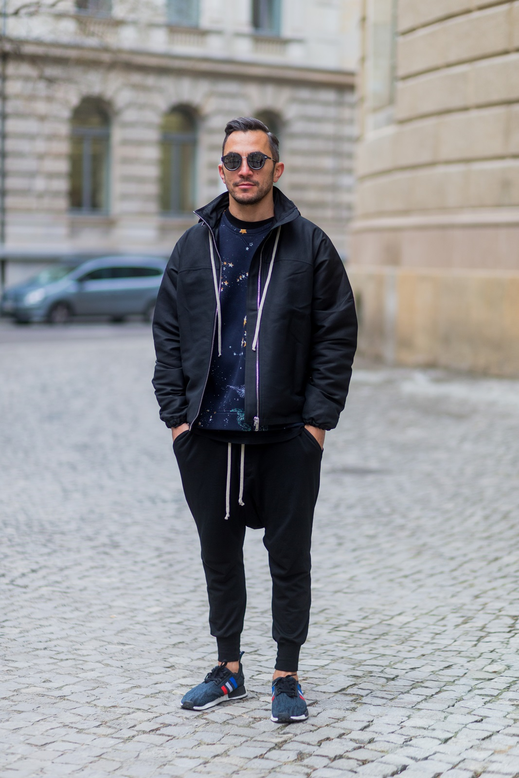 BERLIN, GERMANY - JANUARY 19: Dima wearing RICK OWENS Zipped Jacket, Valentino Cosmo Printed sweatshirt, Rick Owens Cotton harem pants, Adidas NMD R1 sneaker, Dior Magnitude Sunglasses during the Mercedes-Benz Fashion Week Berlin A/W 2017 at Kaufhaus Jandorf on January 19, 2017 in Berlin, Germany. (Photo by Christian Vierig/Getty Images) *** Local Caption *** Dima