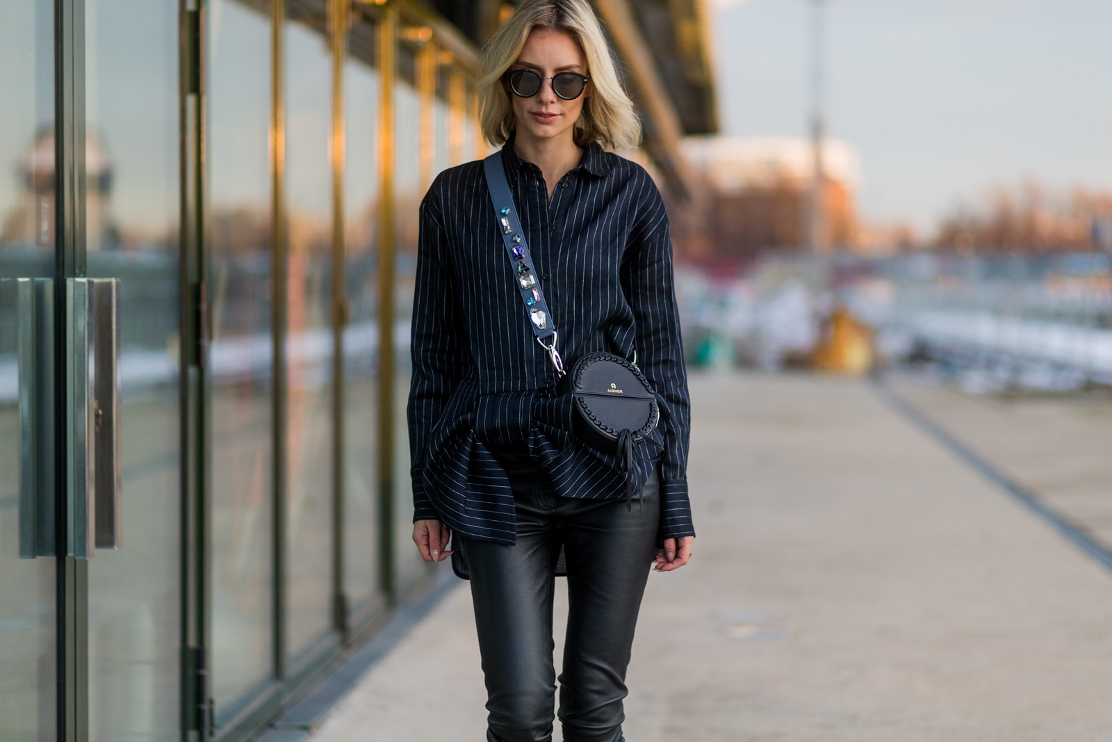 BERLIN, GERMANY - JANUARY 17: Lisa Hahnbueck wearing Victoria Beckham striped blouse with oversized ow tie, Bonvirage leather pants, Aigner bag, Aeyde Bowie Ankle Boots patent leather, sunglasses DIOR MAGNITUDE0 during the Mercedes-Benz Fashion Week Berlin A/W 2017 on January 17, 2017 in Berlin, Germany. (Photo by Christian Vierig/Getty Images) *** Local Caption *** Lisa Hahnbueck