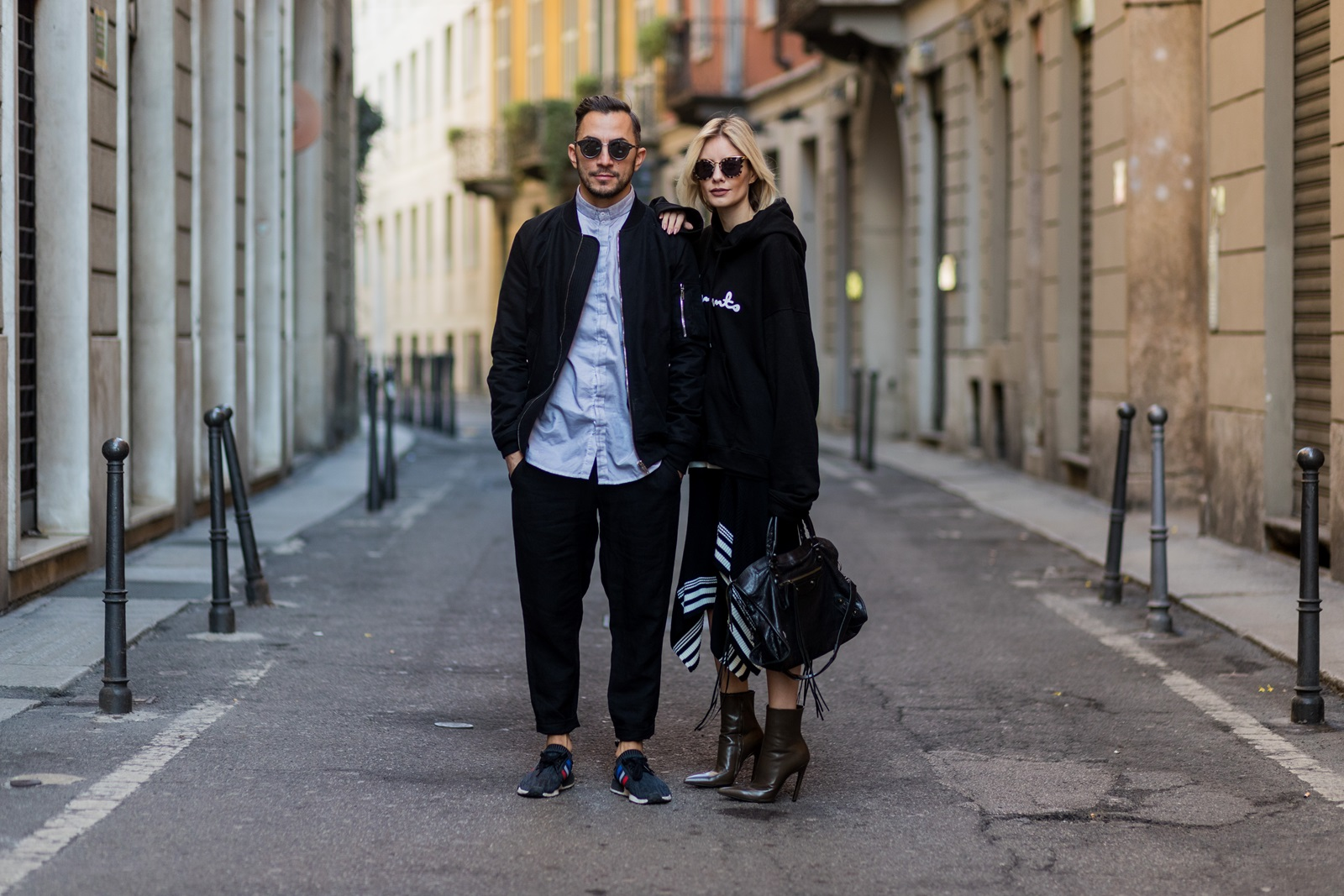 MILAN, ITALY - FEBRUARY 26: Couple Dima wearing Rick Owens Bomberjacket, Boris Sabberi Bidjan Shirt, Rick Owens Loose Pants, Adidas Nmd Sneaker, Dior Magnitude Sunglasses and Lisa Hahnbueck wearing Vetements Sweatshirt, Designers Remix draped rip knit, Balenciaga Boots, Balenciaga Motorcycle bag, Prada Sunglasses during Milan Fashion Week Fall/Winter 2017/18 on February 26, 2017 in Milan, Italy. (Photo by Christian Vierig/Getty Images) *** Local Caption *** Lisa Hahnbueck